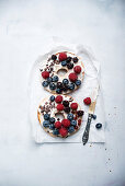 A bagel topped with vegan quark, fresh berries and cocoa nibs