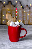 Red cup with cocoa, marshmelow, gingerbread man, star and a straw in a strip on the background of a gingerbread town. Christmas style