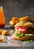 Homemade Vegan Burger with cauliflower beans and vegetable, garnished with pickled red onions and onion rings