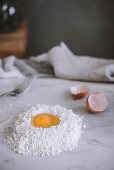 Raw egg lying on heap of flour on marble tabletop