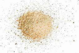 A heaped mixture of kamut and spelt semolina on a white background