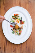 A baked egg on asparagus and tomato salad