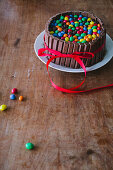 A chocolate cake with chocolate bars on a wooden table with a red ribbon for Mother's Day