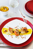 Scallops fried in butter with pumpkin and orange purée, hazelnuts and diced bacon
