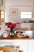 Strauß Rosen, aufgeschlagenes Buch und Kuchen in der Landhausküche