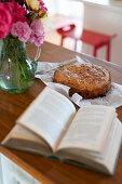 Aufgeschlagenes Buch, Kuchen und bunter Rosenstrauß auf der Theke