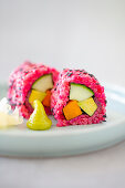 Vegan sushi with beetroot rice, avocado, carrots and cucumbers