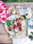 Grilled vegetable skewers with haloumi and baguette with crème fraîche and olive oil