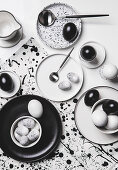 Black, white and speckled eggs on a table with black-and-white crockery