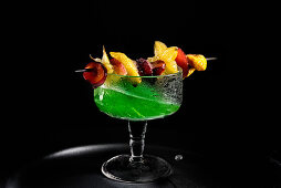 A green drink with an exotic fruit skewer