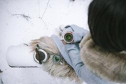 Woman drinking tea in snowy garden