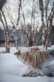 A gingerbread bundt cake with vanilla white glaze on a white rustic table outdoors in the snow