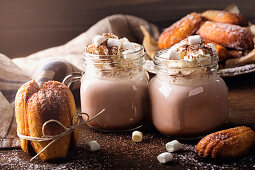 Hot chocolate with whipped cream and marshmallows served with madeleines