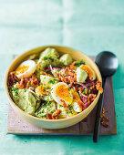 Potato salad with avocado crema, boiled eggs and crispy bacon