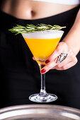 Cocktail mit Eiweißhaube und Rosmarin serviert