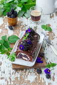 Chocolate roll with cream and blackberries