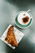 A croissant and a cup of cappuccino