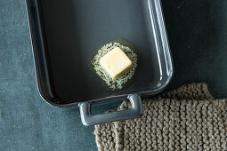 A baking tin being greased with butter