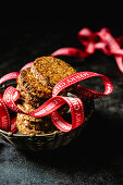 Spiced biscuits with walnuts, dates, coconut flakes and a Christmas ribbon