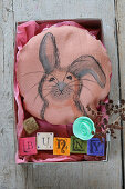 A homemade cushion with a rabbit motif in a box for Easter