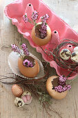 Blown Easter eggs as vases in a pink egg box with purple heather and sugar eggs