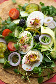 Wraps with deviled eggs, micro herbs, avocado and tomatoes (close up)