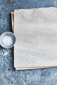 A dish of coarse sea salt next to multiple sheets of paper