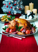 Christmas Turkey with roast red apples and onions with potato wedges and silver Christmas tree
