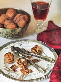 Christmas walnuts cracked open on plate with nut cracker and red wine