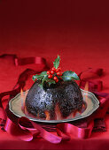 English Christmas pudding with flames and holly garnish on pewter plate