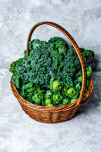Fresh brussels sprouts and kale leaves in a basket