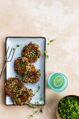 Slow-roasted lamb, tahini and pea fritters