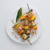 Stockfish skewers with oranges, bay leaves and bacon
