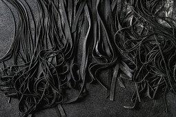 Frische selbstgemachte Sepiatagliatelle und Sepiaspaghetti (Aufsicht)