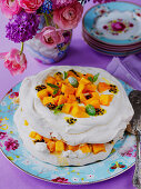 Easter mango and passion fruit pavlova with mint leaves with vase of Sporing flowers