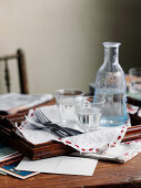 A carafe of water and water glasses on a wooden tray on a desk