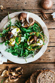 Two bruschette with olive oil ruccola and mushrooms on a wooden plate