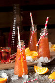 Bottles of Aperol Cocktails with Orange Wedges and Ice