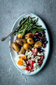 Antipasti platter with beans, potatoes, olives, egg and Greek salad