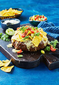 Baked meatloaf with cheese, nachos, tomatoes and avocado