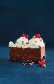 A slice of chocolate mousse cake with coconut, cream and raspberries