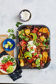 Baked nachos with chili con carne, avocado, coriander and sliced chillies