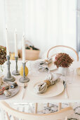 Autumnal arrangement of hydrangeas and candlesticks on table