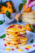 Pancake with Mandarin oranges, pomegranate seeds and maple syrup pouring from a spoon