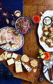 A Christmas buffet with ham, coleslaw, baked potatoes, cheese and crackers