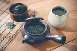 Green tea in a pot and a mug