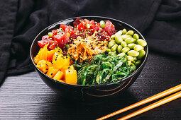 A poke bowl with tuna fish, mango, algae and edamame (Asia)