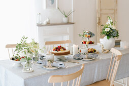 Cakes, berries and madeleines on table festively set for afternoon coffee