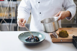 A chef serving cooked mussels on a plate