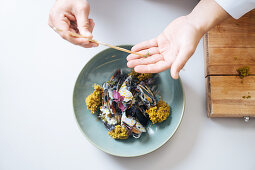 A chef garnishing a mussel dish (top view)